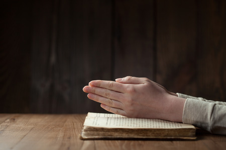 prayer: Hands folded in prayer over open russian Holy Bible