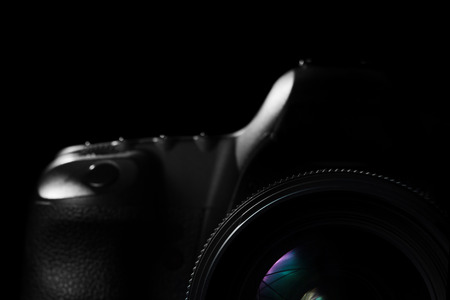 camera: Image of a professional modern DSLR camera low key image  Modern DSLR camera with a very wide aperture lens on in a dark space. Top part of a camera is visible and the rest goes into the shadow Stock Photo