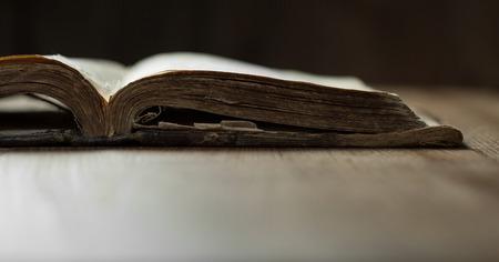 biblia: Imagen de un viejo Santa Biblia en el fondo de madera en un espacio oscuro Foto de archivo
