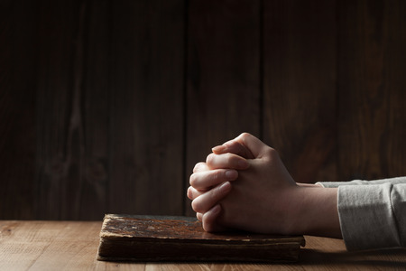 manos orando: Manos femeninas en la Biblia sobre fondo de madera Foto de archivo