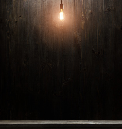 thomas: wooden interior room with classic Edison light bulb on wooden background switched on. retro edison light bulb