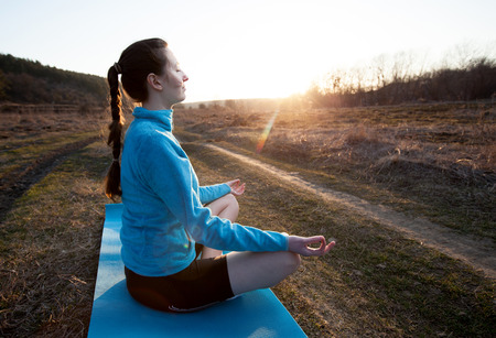 strength training: Brunette woman practicing yoga outside during sunset wearing sports wear with eyes closed Stock Photo