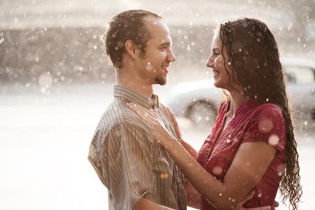 mojar: El amor en la lluvia. Chico y una chica bes�ndose en la lluvia Foto de archivo