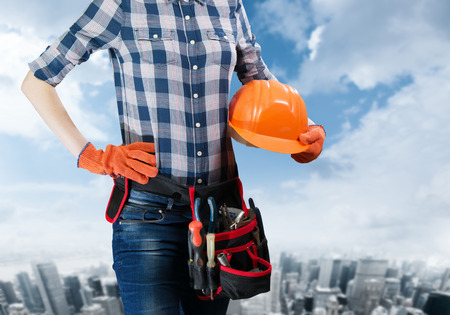 toolbelt: woman engineer holding a helmet with toolbelt with the city background for a sign