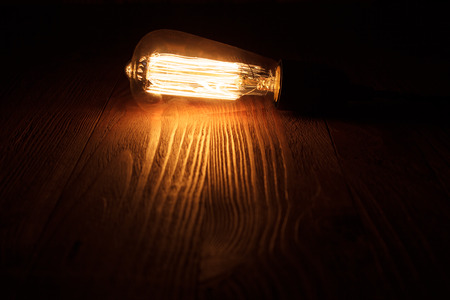 thomas: A classic Edison light bulb on wooden background switched on. retro edison light bulb