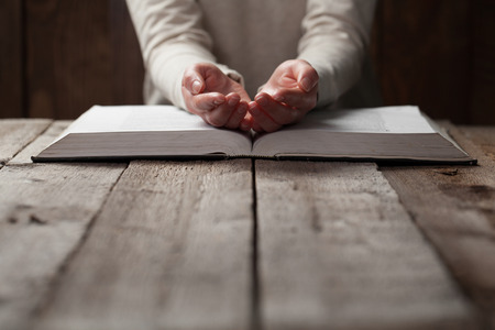 woman hands on bible. she is reading and praying over bible in a dark space over wooden table