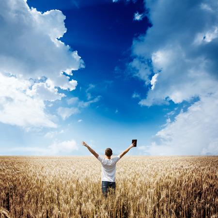 leer biblia: hombre sosteniendo Biblia en un campo de trigo