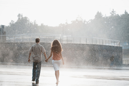 sexual couple: couple in love hugging and kissing under summer rain