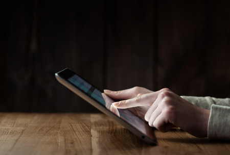 woman  hand: woman hand presses on screen digital tablet over wooden table