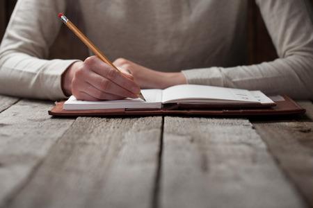 mano escribe con una pluma en un cuaderno Foto de archivo