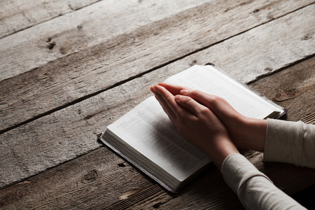 plead: Woman hands praying with a bible in a dark over wooden table