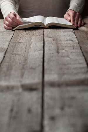 biblia: Mujer que lee la biblia en la oscuridad sobre la mesa de madera Foto de archivo