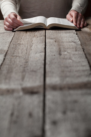 holy bible: woman reading the bible in the darkness over wooden table