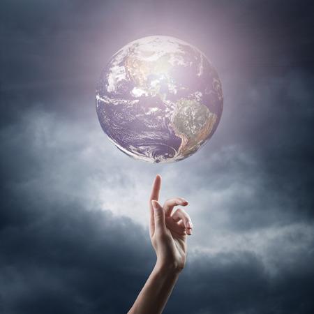 cristianismo: mano apuntando al planeta en el espacio. Elementos de esta imagen proporcionada por la NASA están Foto de archivo