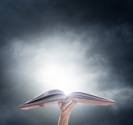 Hand holding o pened magic book with magic light. Education Stockfoto