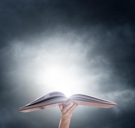 magie: Une main tenant o livre magique PENED avec la lumière magique. Éducation