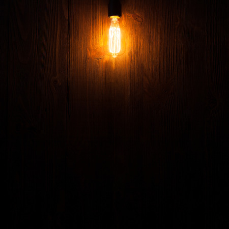A classic Edison light bulb on wooden background switched on. retro edison light bulb photo