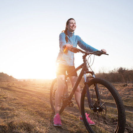 outdoor fitness: Close up of woman riding mountain bike at sunset in the nature wearing sport wear