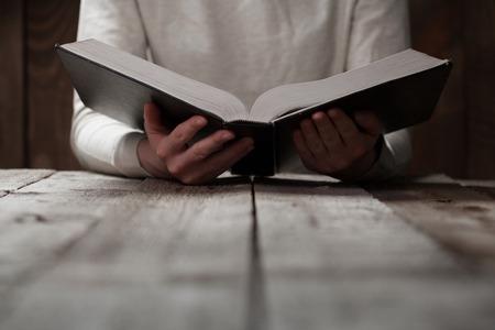 orando: manos de la mujer en la biblia. que está leyendo y orando sobre la biblia en un espacio oscuro sobre la mesa de madera