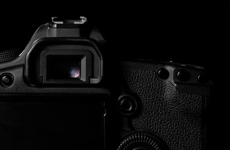 eos: Image of a professional modern DSLR camera low key image  Modern DSLR camera  in a dark space. Top part of a camera is visible and the rest goes into the shadow