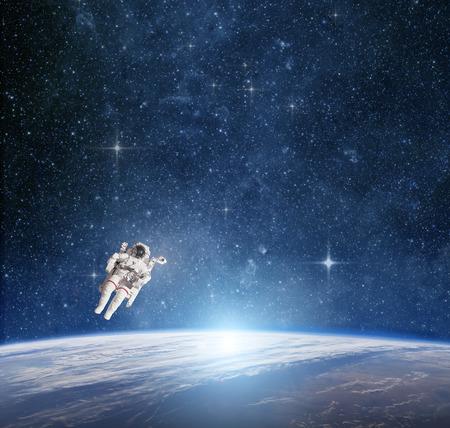 cohetes: Astronauta en el espacio exterior contra el planeta tierra.