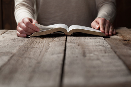Mujer que lee la biblia en la oscuridad sobre la mesa de madera Foto de archivo