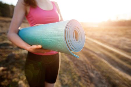 saludable: mujer caminando con una estera de yoga al aire libre durante la puesta del sol na zona rural vistiendo ropa deportiva y haciendo yoga