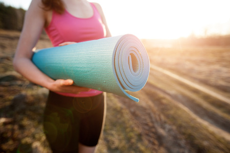 yoga sunset: woman walking with a yoga mat outside during sunset n a rural area wearing sports wear and doing yoga Stock Photo