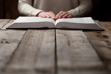 bible ouverte: femme, mains sur la Bible. elle est en train de lire et de prier sur bible dans un espace sombre sur la table en bois