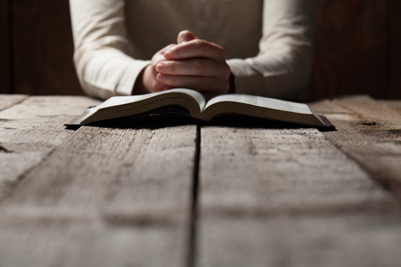 religious: Woman hands praying with a bible in a dark over wooden table