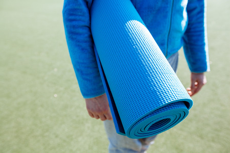 yoga pants: A woman walking with a yoga mat Stock Photo