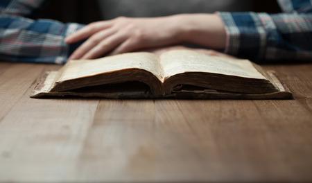 biblia: Mujer que lee la biblia en la oscuridad sobre la mesa de madera. Biblia se abre en una mesa