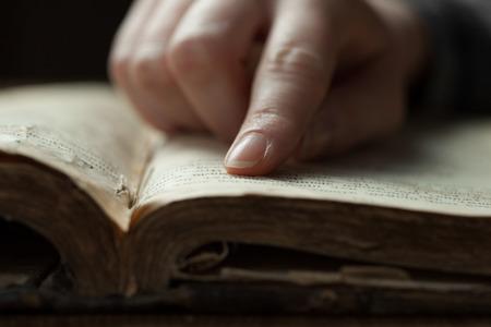 vrouw vinger drukt op oude bijbel boek in een donkere romm over houten tafel en lezen