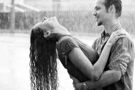 Love in the rain. Boy and a girl kissing and hugging in the warm summer rain. Boy is holding a girl with his hands by her wrist while she is listing her head up and smilind. It is raing outside