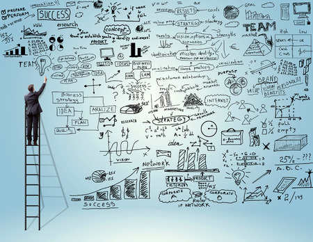 man writing: businessman standing on ladder and drawing on a business plan Stock Photo