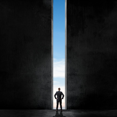 possibility: Silhouette of businessman standing in a gap of air in a dark room