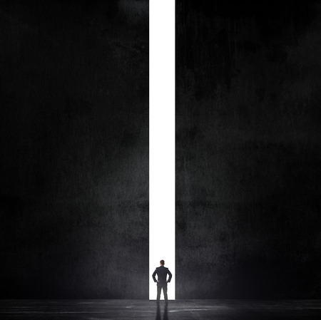 Silhouette of businessman standing in a gap of air in a dark room