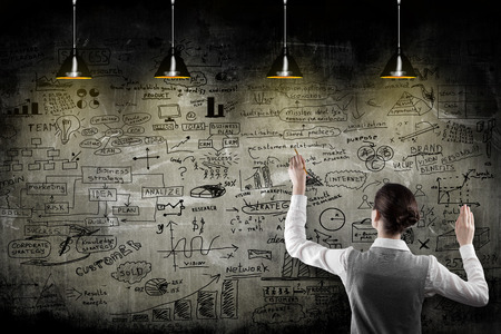 estrategia: Mujer de negocios con la estrategia en la pared
