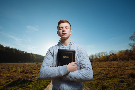 Young man holding Bible in a park Standard-Bild