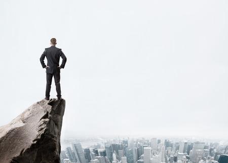 Jonge zakenman die zich op de rand van rock bergen en kijken naar de stad