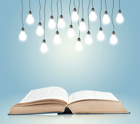 law books: Open book with shining lamps Stock Photo
