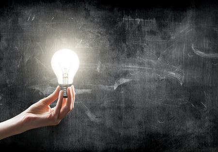 kilowatt: businesswoman holding Light bulb lamp on blackboard background with copy space