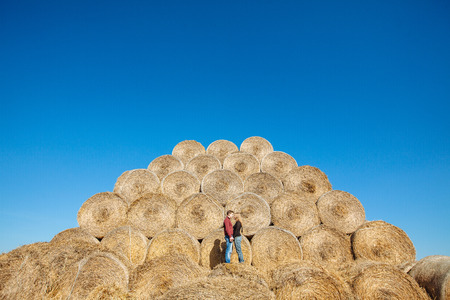 facing each other: couple standing on a haystacks facing each other