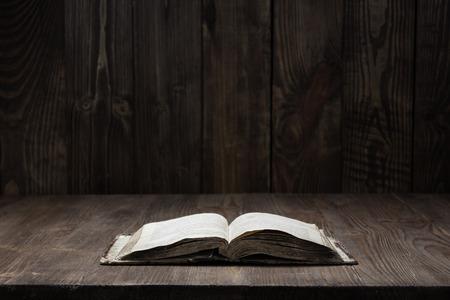 暗闇の中で木製の背景に木製の背景に古い聖書のイメージ