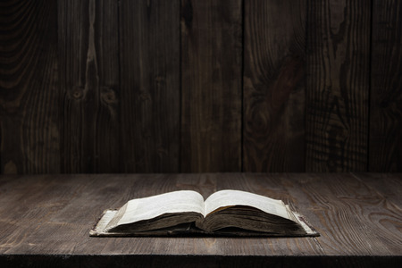 Image of an old  Holy Bible on wooden background on a wooden background in a dark space
