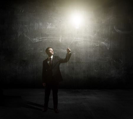 Young man holding a light at his hands against dark background photo