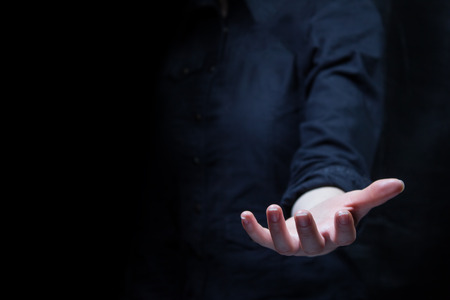 female hand holding showing or giving something over black background