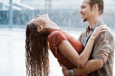 mojada: El amor en la lluvia. Chico y una chica besándose en la lluvia Foto de archivo