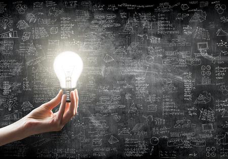 estrategia: sosteniendo la mano o mostrando una bombilla delante de idea de negocio concepto en la pared tablero blackground