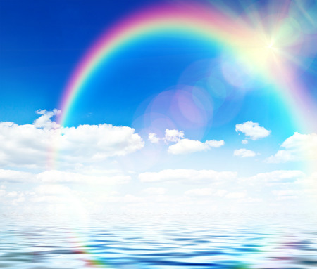 Blue sky background with rainbow and reflection in water